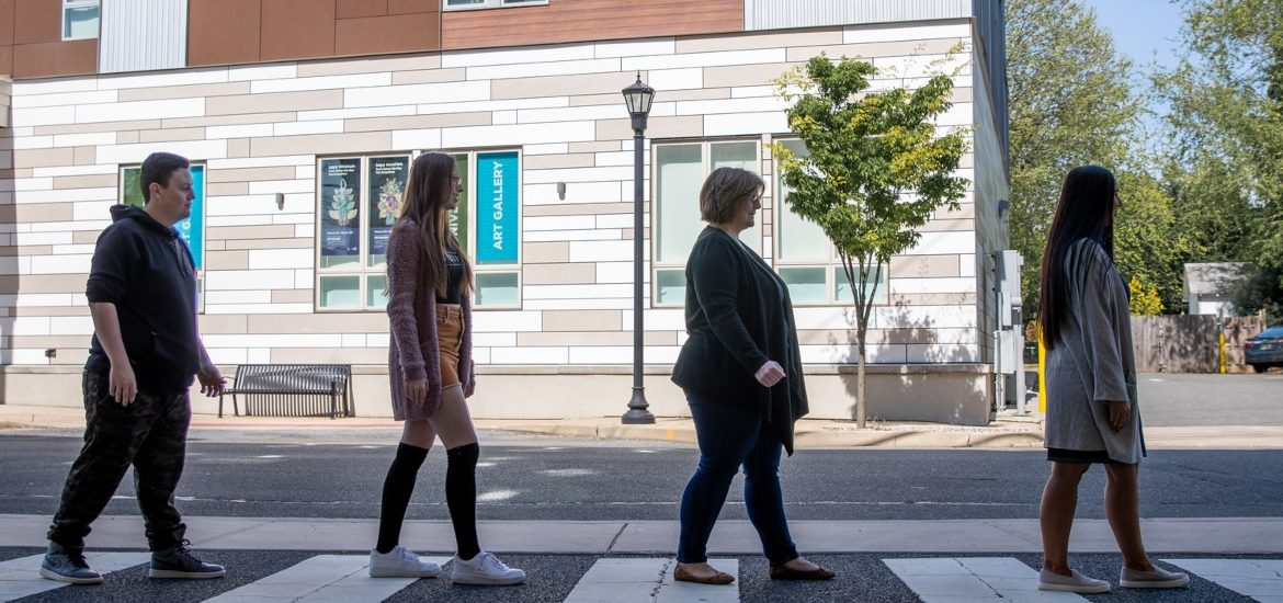 Lisa Fagan and her students walk in the crosswalk in Abbey Road fashion.