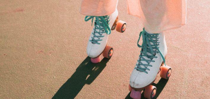 A GIRL WEARING WHITE IMPALA QUAD ROLLER SKATES ON A TENNIS COURT (RETRO/VINTAGE AESTHETIC).