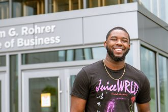 Reshaun smiles and stands in front of the entrance to Business Hall.