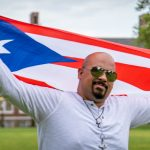 Brandon holding the Dominican Republic flag in front of Bunce hall.