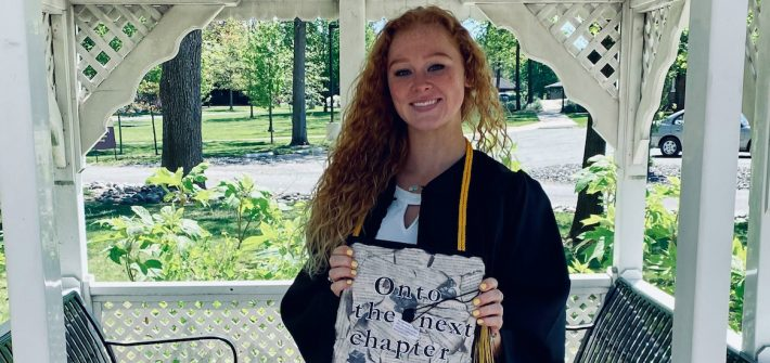 Chloe holds her decorated cap inside a gazebo on campus.