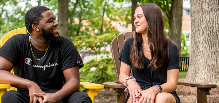 Natalie sits with her coworker Reshaun on campus.