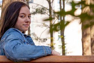 Lexi sits on a campus bench and looks over her shoulder.