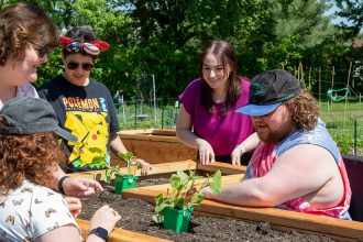 The Borgerson family and Jenna see the raised beds at the Williamstown Organic Community Garden.