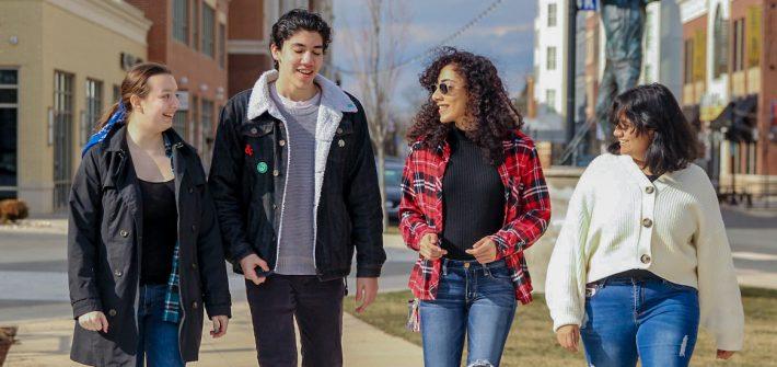 Four students wearing warm autumn clothing walking down a sidewalk on Rowan Boulevard.