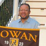 Byron holds a Rowan University flag.
